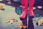 Woman with pink rain boots jumps into a puddle on rainy autumn day. Toned image