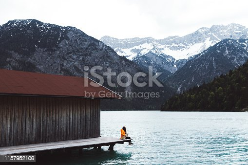 Young woman in orange raincoat and her small fluffy cute pug enjoying summer sunset at beautiful mountain lake sitting on the pier near boat hut with view of snowcapped mountains