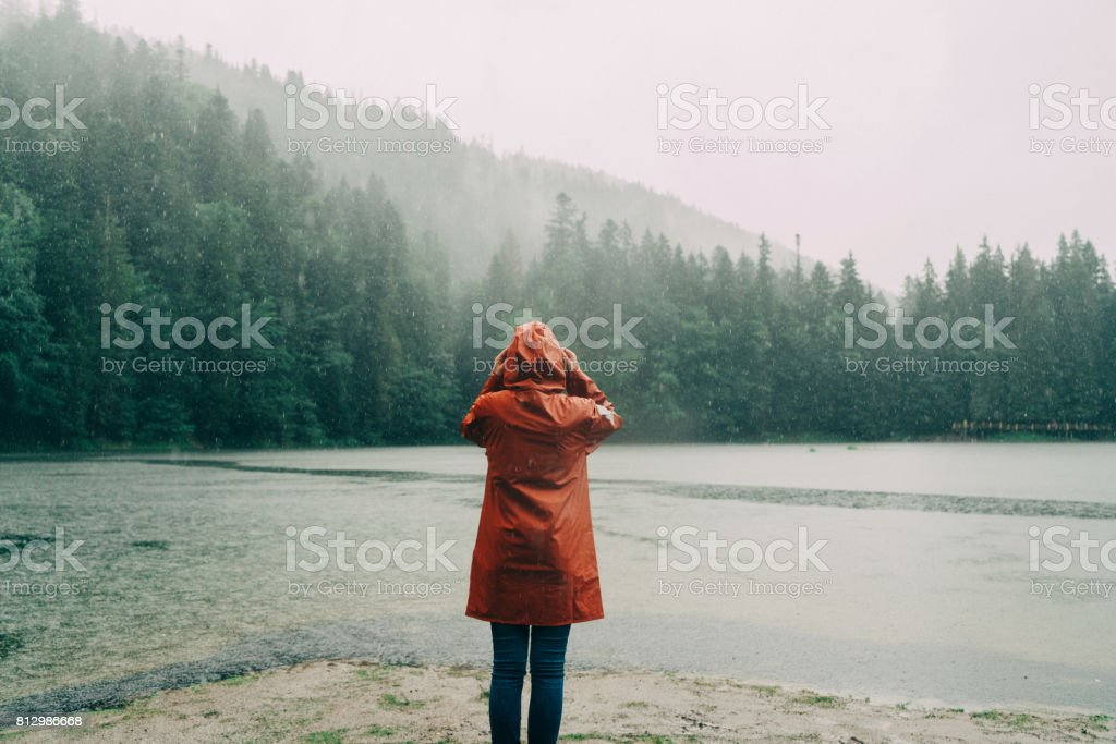 Woman in raincoat standing near the lake under the pouring rain stock photo