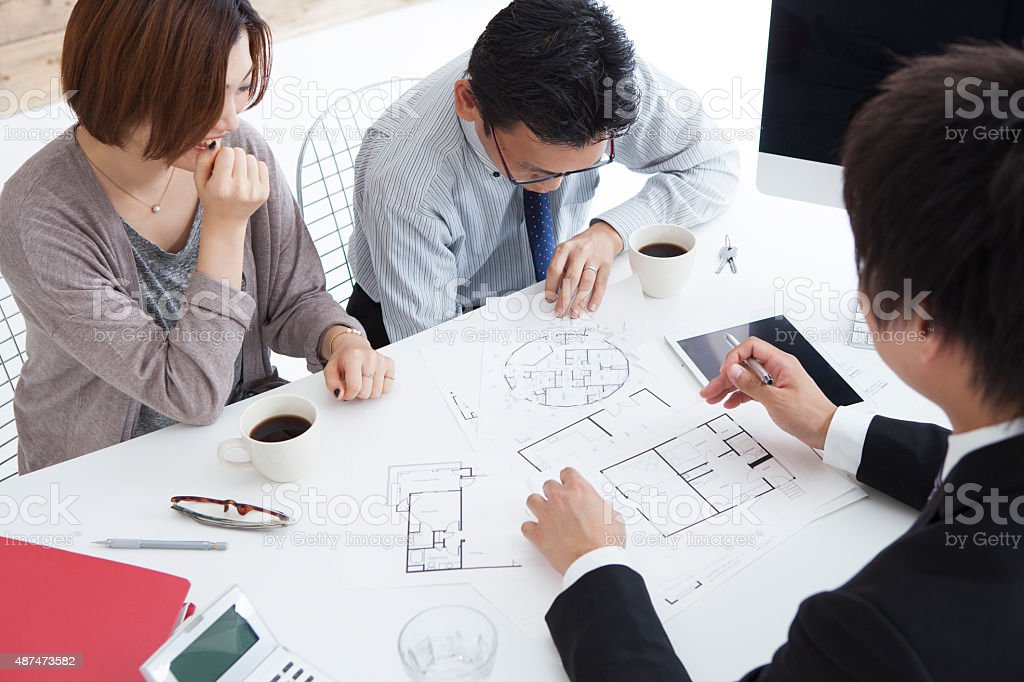 Woman in real-estate agency talking to construction planner stock photo