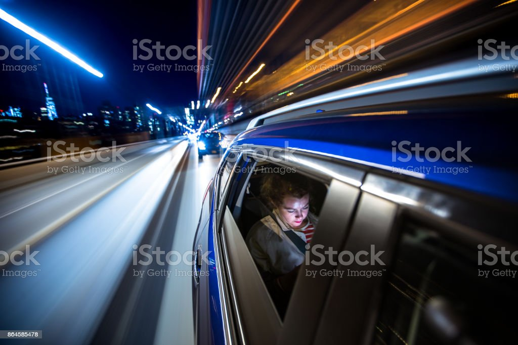 Woman in Rear of Car Driving Through New York City stock photo