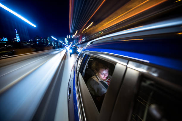 woman in rear of car driving through new york city - rideshare stock photos and pictures