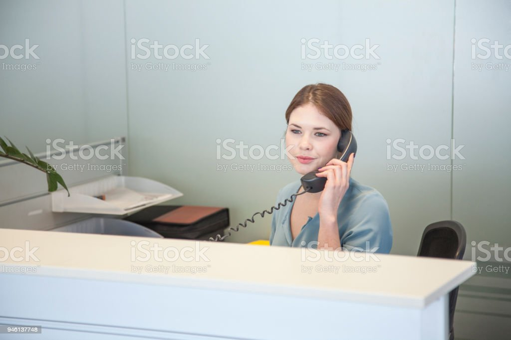 Woman in reception talking on phone stock photo