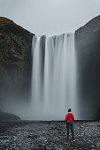 A woman in red standing below Skogafoss Waterfall in Iceland.