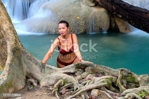 Woman in red bikini happy at Erawan Waterfall and natural in Kanchanaburi province Thailand. Erawan Waterfall Is a beautiful and famous water fall.