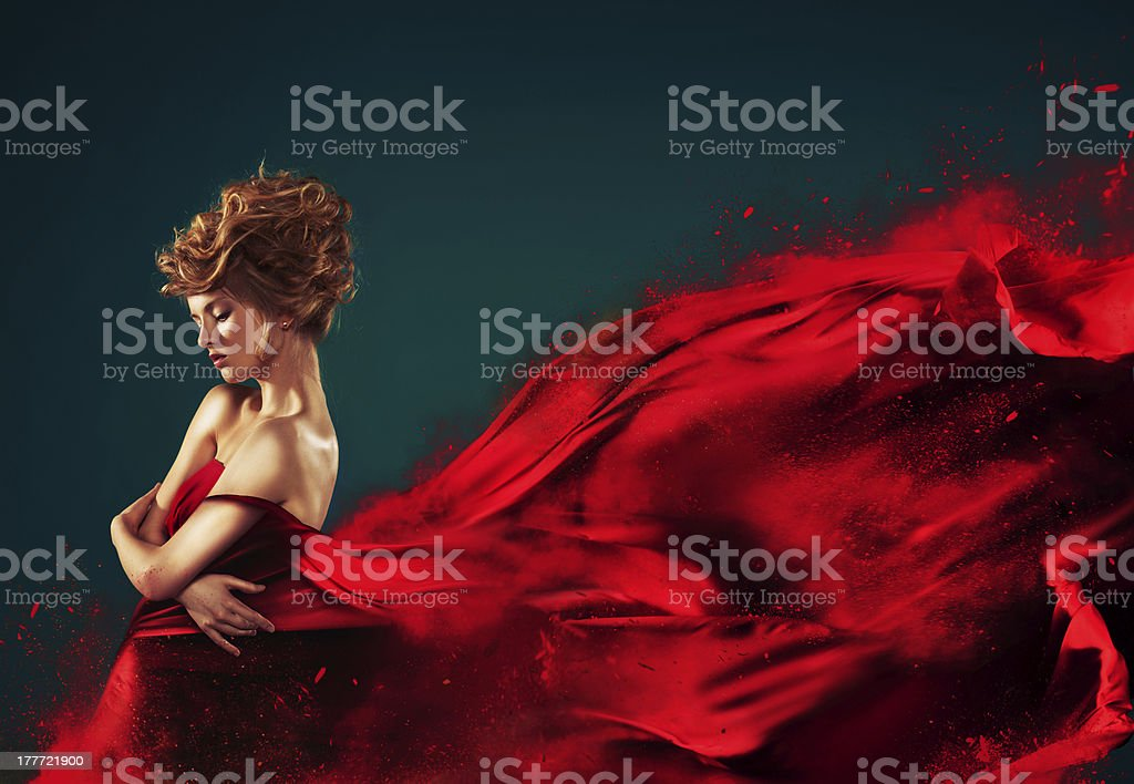 Woman in red blowing flying dress dissolving splash stock photo