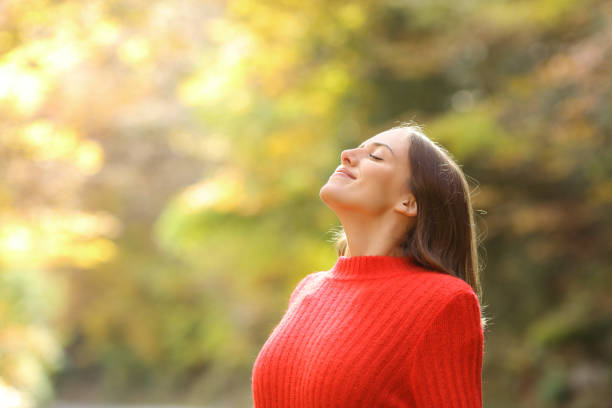 Woman in red breathing fresh air in autumn in a forest stock photo
