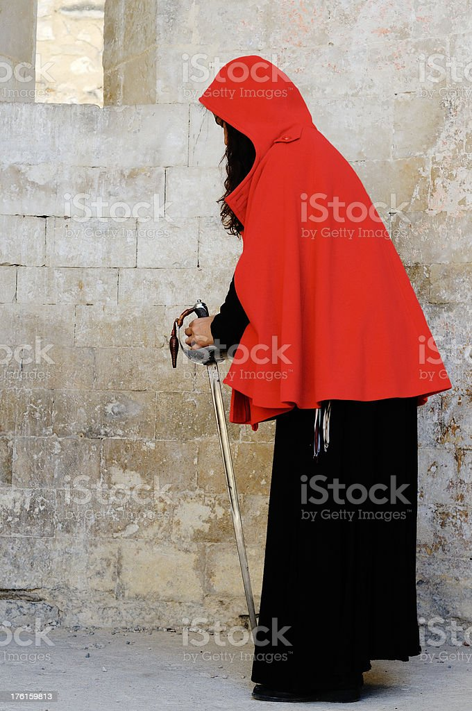 woman in red cape with sword stock photo