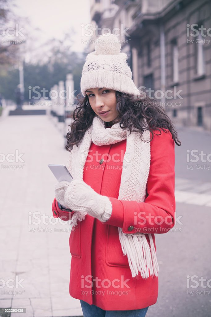 Woman In Red Coat And Wool Cap With Smartphone stock photo ...