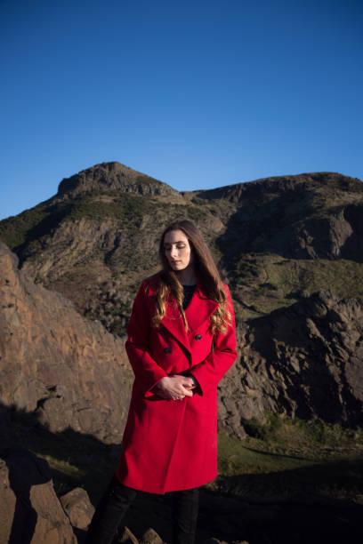 Woman in red coat in an outdoors scenic location stock photo