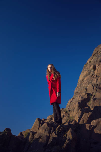 Woman in red coat looking over cliff edge. stock photo
