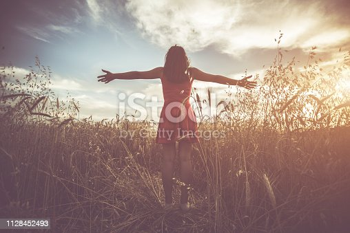Young woman in red dress and spread hands relaxing in meadow with high grass.