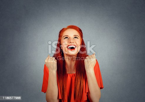 portrait happy redhead woman in red dress exults pumping fists ecstatic celebrates success isolated on a red background. exulting for a reason concept