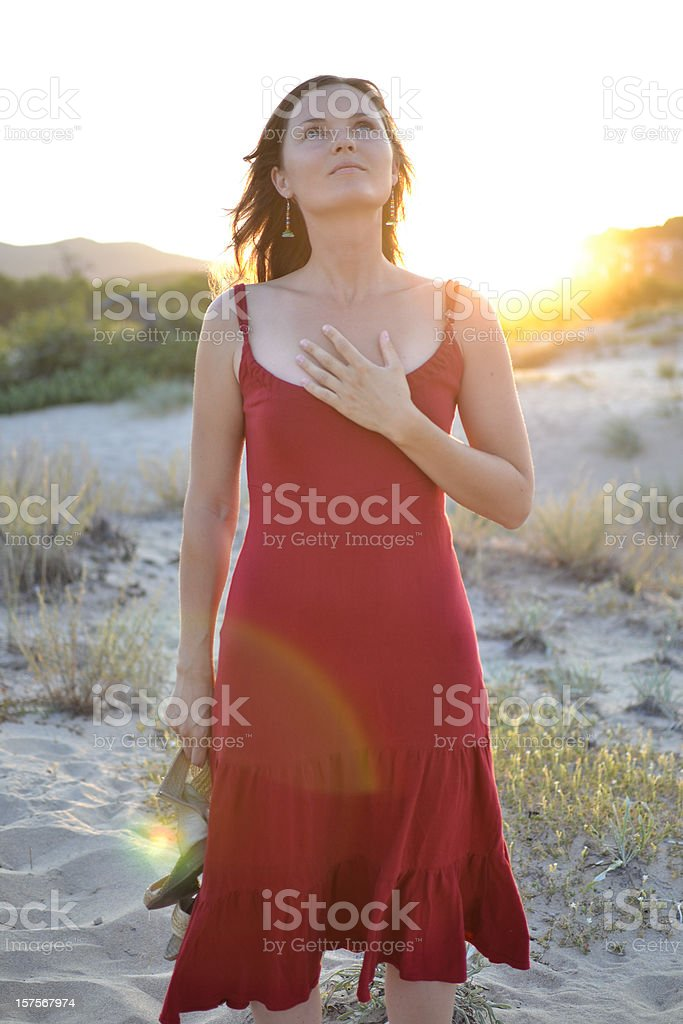 Woman in red dress on the beach with hand over her heart stock photo