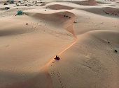 Woman in red dress on the desert sand dunes at sunset