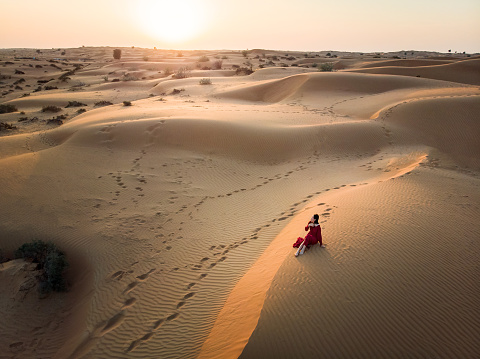 Woman in red dress on the desert sand dunes