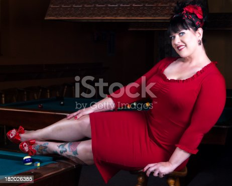 A beautiful and voluptuous woman in a bright red dress sitting on a stool with her feet up on a pool table in a pin-up style pose. SnS'lypse.