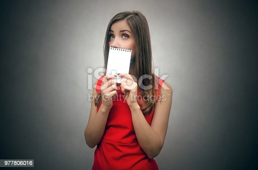 Woman is holding in hands a empty notepad with copy space. Contact us card template. Greeting card message.