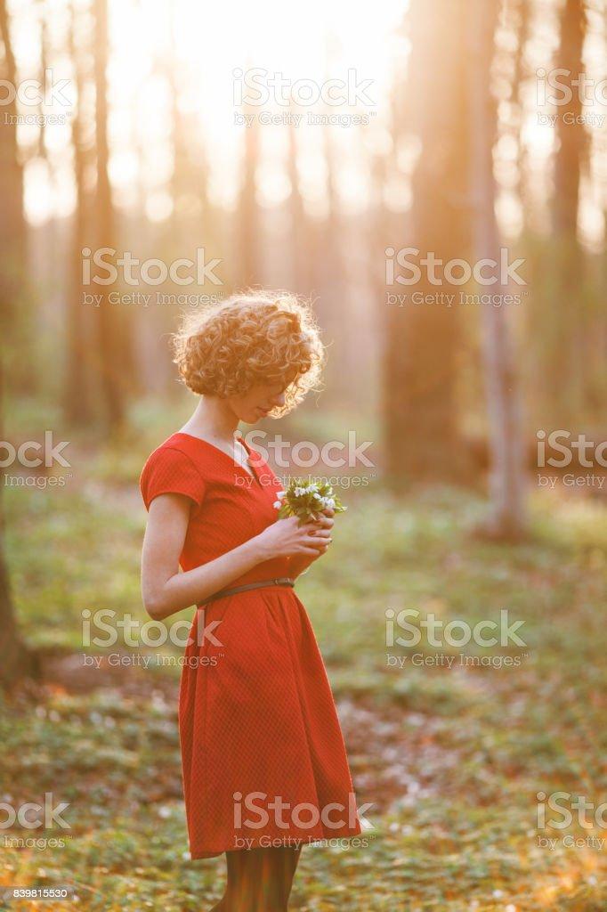 Femme en robe rouge debout dans la forêt avec bouquet - Photo