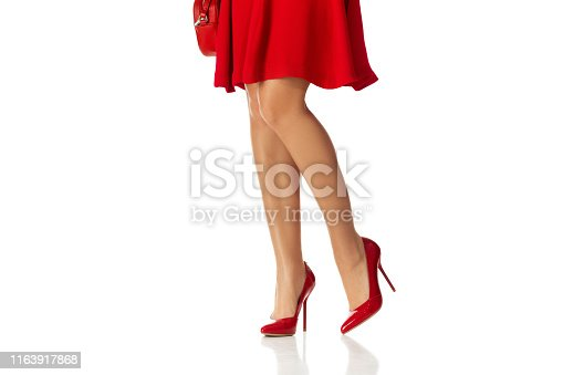 Woman in red dress and high heels shoes isolated on white background.