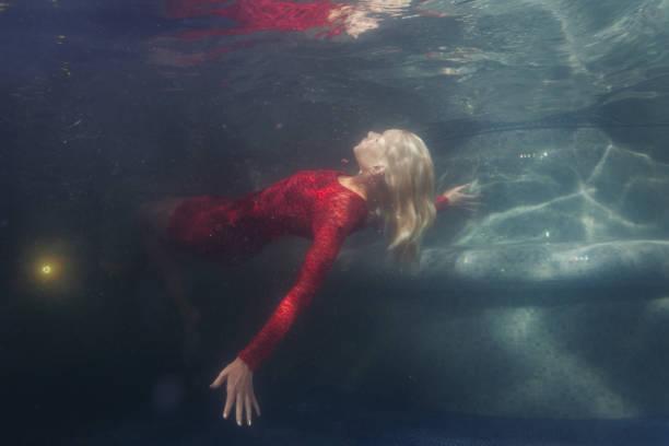 woman in red dress under water. - frau tiefer ausschnitt stock-fotos und bilder