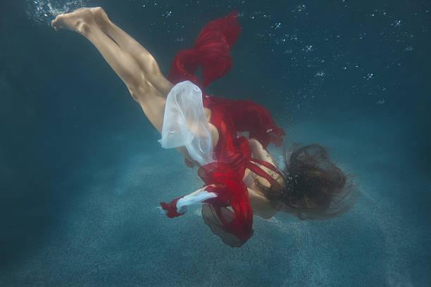 frau im roten kleid unter wasser. - meerjungfrau kleid stock-fotos und bilder