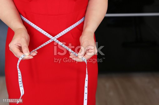 1184112328 istock photo Woman in red dress with measuring tape around the waist 1173322328