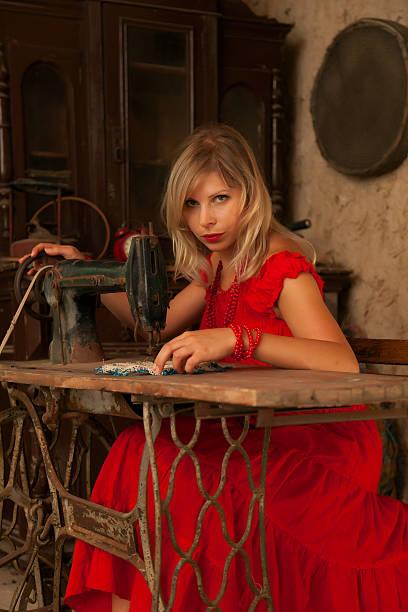 frau im roten kleid, die auf alte nähmaschine - nähmaschinenschrank stock-fotos und bilder