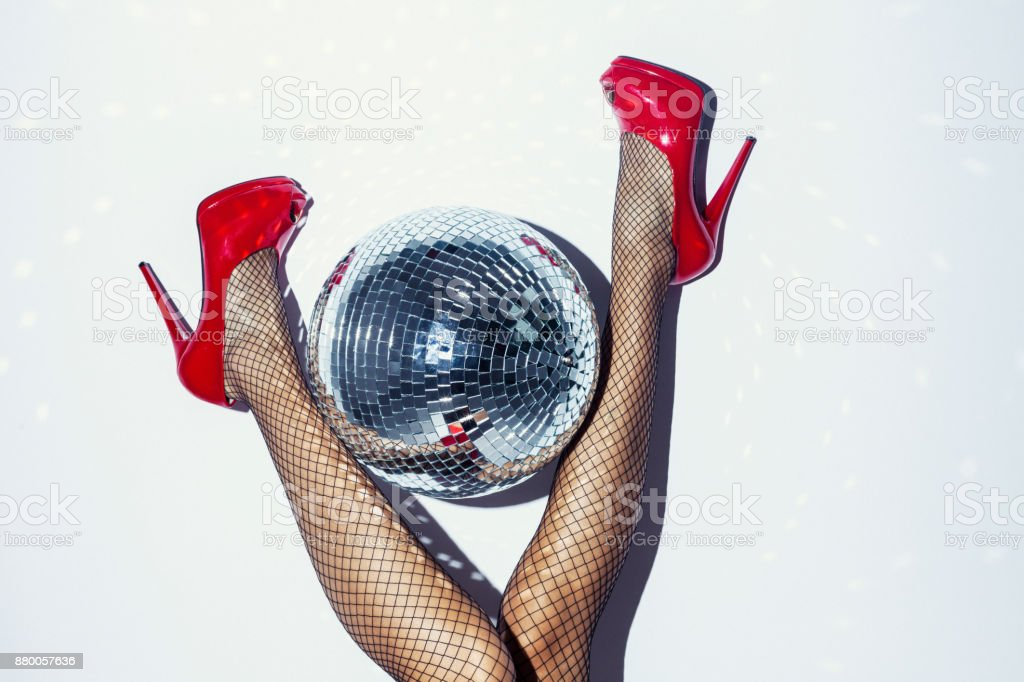 Woman in red heels and disco ball stock photo