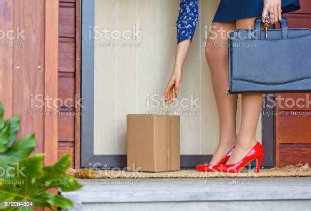 Woman in red heels collects parcel at front door of home picture id872264324?b=1&k=6&m=872264324&s=612x612&h=zropib3edaveh1x77r e1szhx0p2yn1kcinguhag5no=