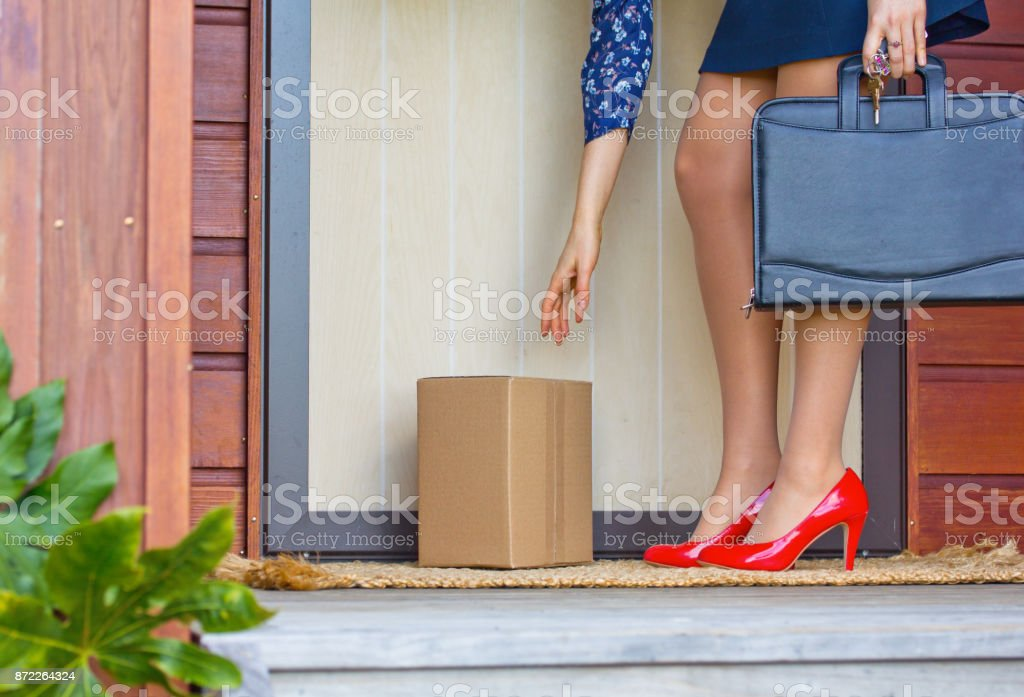Woman in Red Heels collects parcel at front door of home stock photo