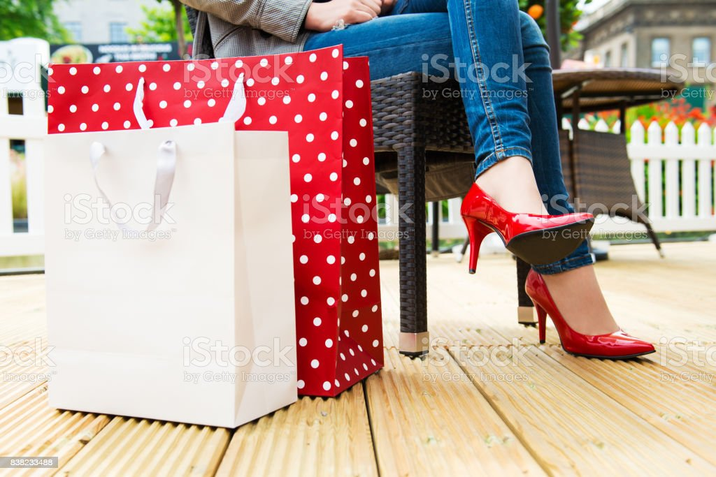 Woman in red high heels taking break after successful shopping stock photo
