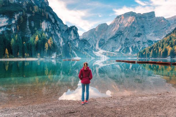 Frau in rot Jacke steht auf der Küste der Pragser Wildsee bei Sonnenaufgang im Herbst. Dolomiten, Italien. Landschaft mit Mädchen, berühmten See mit schönen Spiegelung im Wasser, Bäume, Himmel mit Wolken. reise – Foto