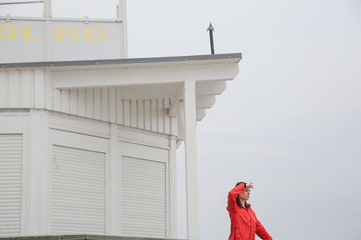 Woman in red jacket standing on the wooden lifeguard tower station