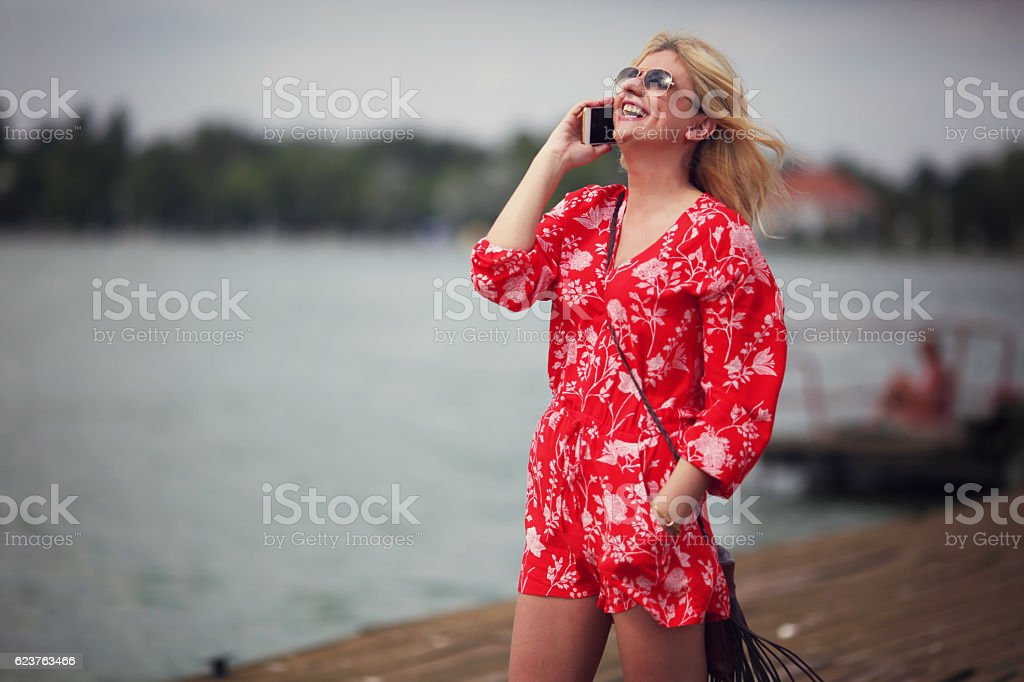 Woman in red jumpsuit at lake stock photo