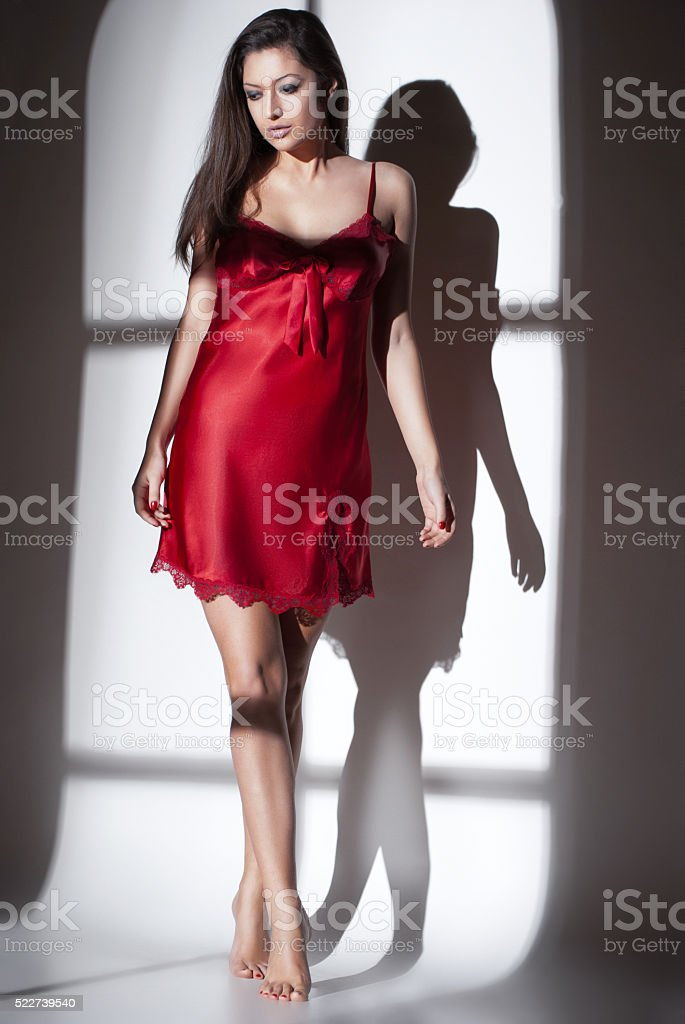 woman in red nightdress with light of window stock photo