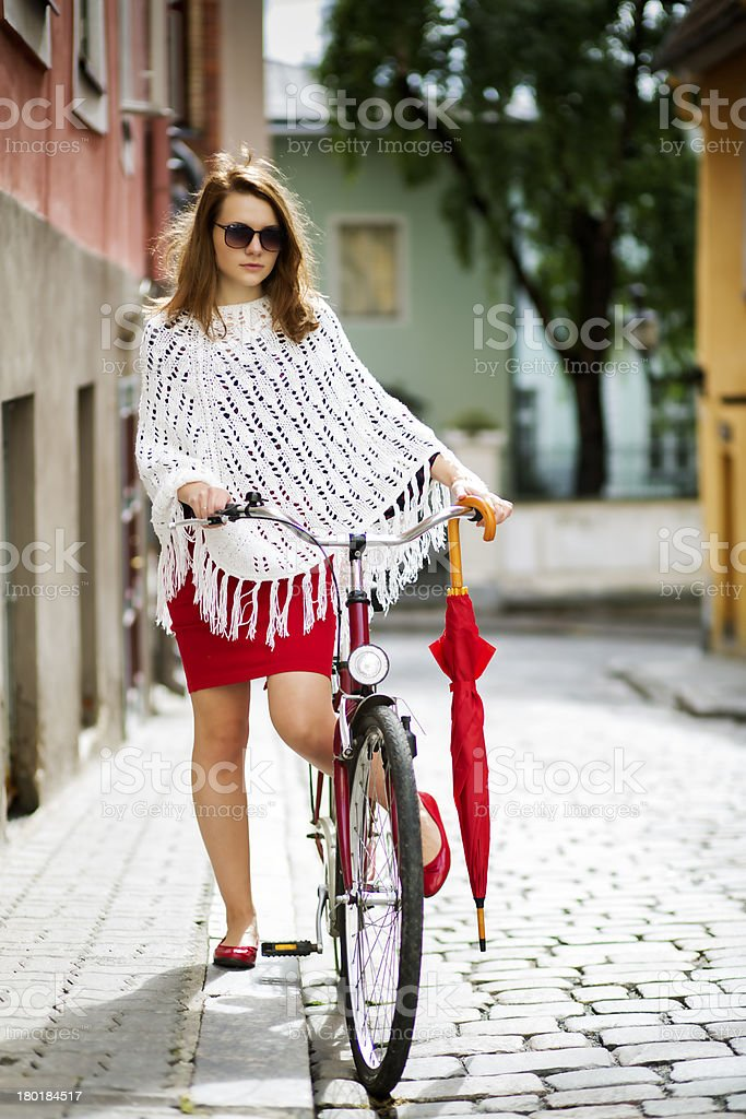 Woman in red put leg on bicycle royalty-free stock photo