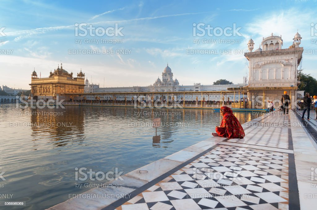 Woman in red saree sits and pray in Golden Temple stock photo