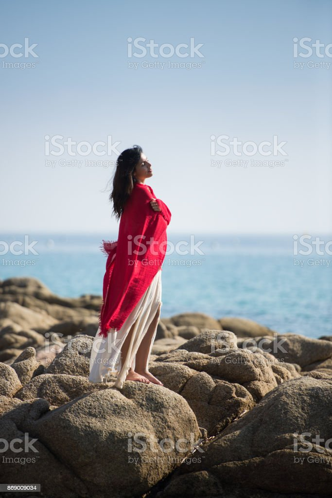 Woman in Red Scarf, Hugging Relaxed, Happy at Sea Shore stock photo