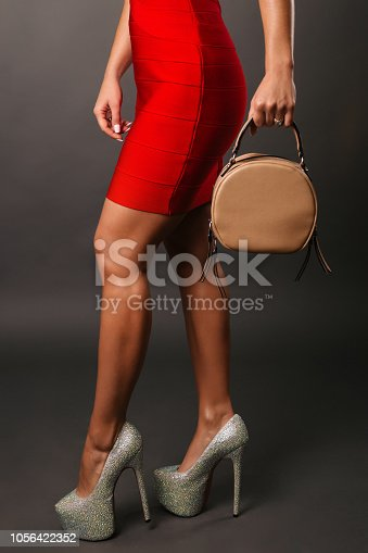 istock Woman in red short dress red spiked shoes holding handbag, female legs in high heels 1056422352