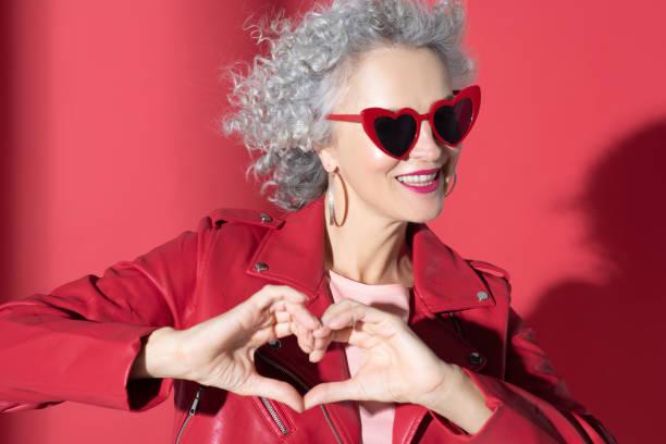 frau in roter sonnenbrille und jacke lächelnd breit - sex sexuelle themen stock-fotos und bilder
