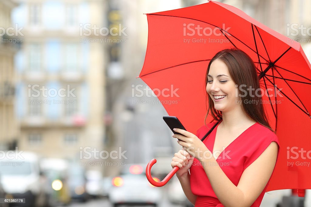 Woman in red texting on a smart phone stock photo