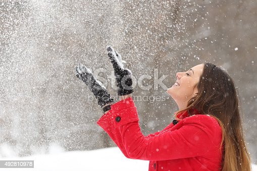 istock Woman in red throwing snow in the air in winter 492810978