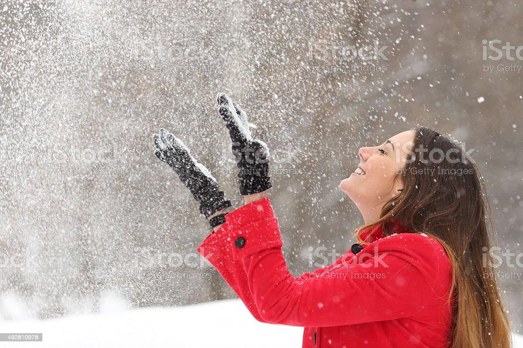Mulher em vermelho arremesso de neve no ar no inverno - foto de acervo