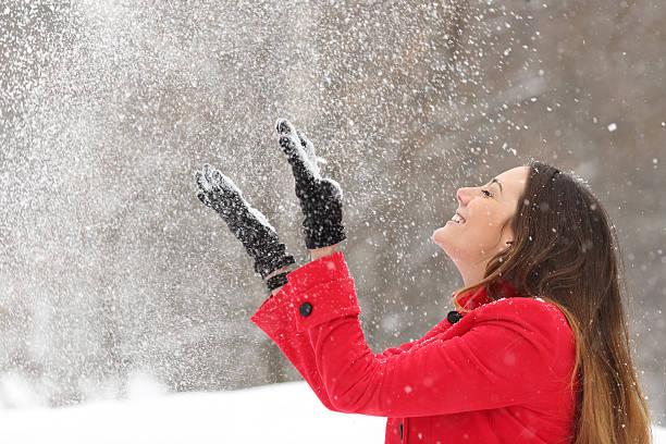 frau in rot werfen schnee in der luft im winter - dynamische posen stock-fotos und bilder