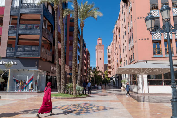 Woman in red walks through new town Marrakesh stock photo