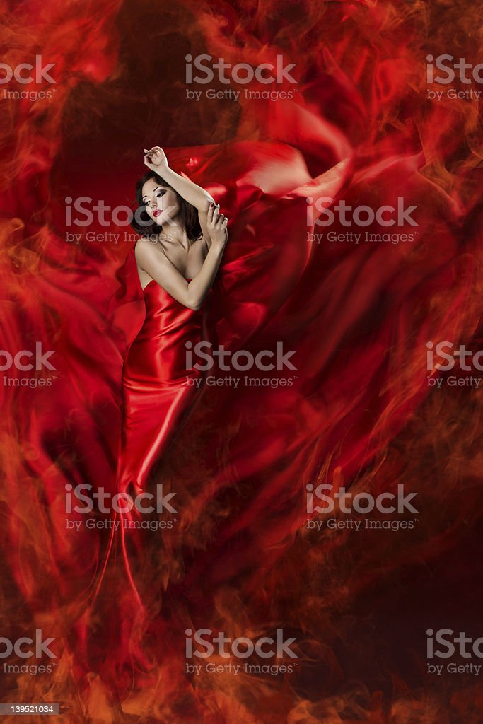 woman in red waving dress as a fire flame stock photo