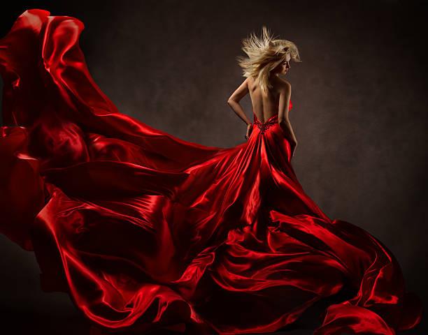 frau in roten wogende kleid tanzen mit fliegenden stoff - lange abendkleider stock-fotos und bilder