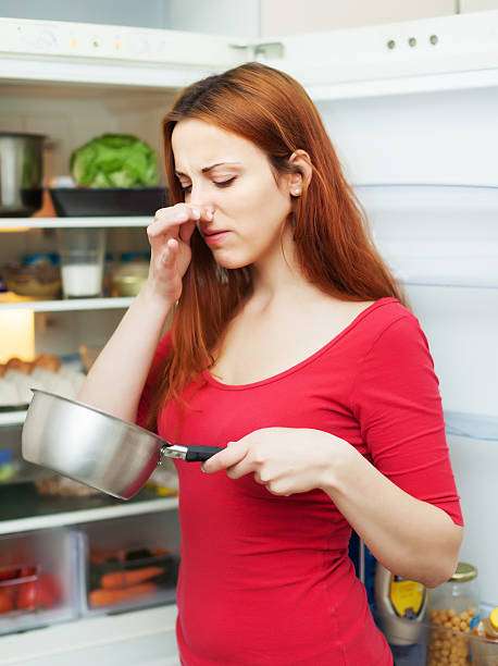 woman in red with foul food woman in red with foul food near   refrigerator addle stock pictures, royalty-free photos & images
