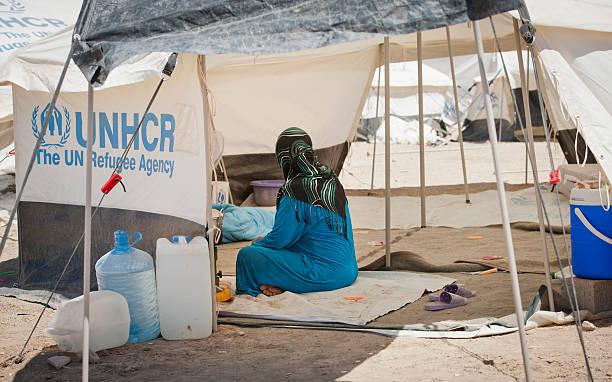 mujer en un campo de refugiados - ayuda humanitaria fotografías e imágenes de stock